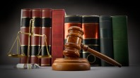 Scales of justice, law books and gavel over dark background