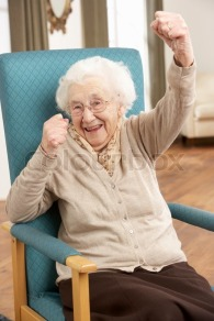 1985238-senior-woman-celebrating-in-chair-at-home
